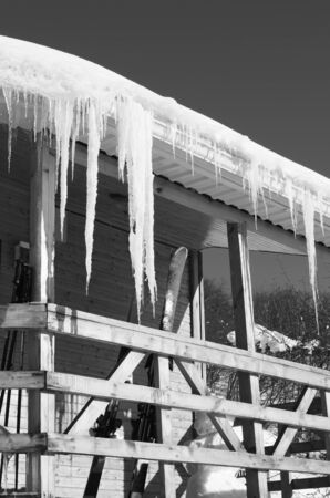 Wooden house with snow cornice and big icicles on roof and ski equipment on balcony at sun winter day. Black and white toned image.