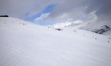 Skiers and snowboarders on trace for ski prepared by snowcat and blue sky with dark clouds in snowy high mountains at gray winter day