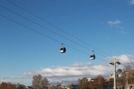 Cableway from Park Rike to ancient fortress Narikala in center Tbilisi, capital of Georgia. City, mountains and blue sky with clouds at background. 報道画像