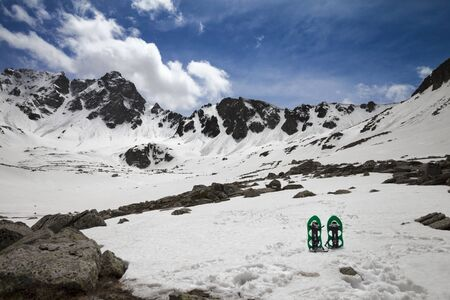 Pair of green snowshoes in snow. High snowy mountains and blue sky with clouds at sunny day. Turkey, Kachkar Mountains, highest part of Pontic Mountains. Wide angle view. Remote location.
