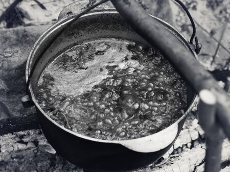 Borscht - Ukrainian traditional soup cooking in old sooty cauldron on campfire at summer day. Black and white toned image.