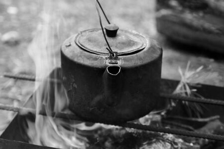 Sooty old teakettle on bonfire with smoke at forest in sunny summer day. Selective focus. Black and white toned image.