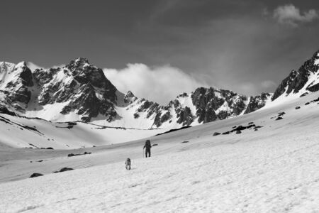 Dog and trekker on snowy plateau in high mountains and sky with clouds at sunny day. Turkey, Kachkar Mountains, highest part of Pontic Mountains. Black and white toned landscape. Banque d'images