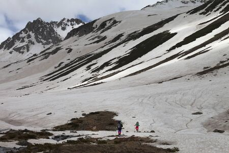 Silhouette of two hikers and dog on snow covered glacier with ground in spring snowy mountains at gray evening. Turkey, Kachkar Mountains (highest part of Pontic Mountains). Remote location.