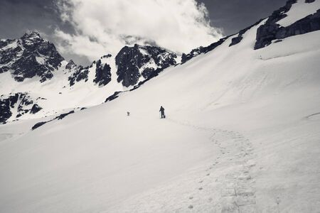Hiker in snowshoes with dog in high snowy mountain at gray day. Turkey, Kachkar Mountains, highest part of Pontic Mountains. Black and white retro toned landscape. Banque d'images