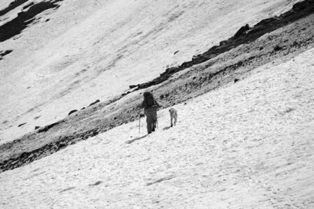 Hiker with dog on snowy glacier and dirty avalanche trace at high mountains. Black and white retro toned landscape.