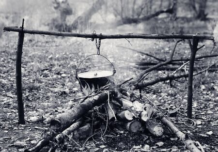 Cooking in old sooty cauldron on campfire at forest. Black and white retro toned image.