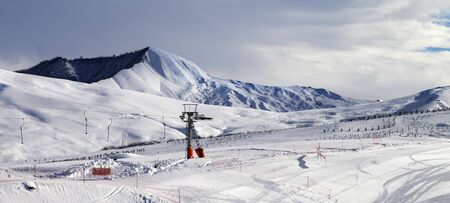Snowy ski slope with surface lift and gray sky at winter. Greater Caucasus Mountains, Shahdagh Azerbaijan. Panoramic view.