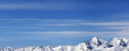 Panoramic view on high snowy mountains and blue sky with clouds at sunny winter day. Caucasus Mountains, Georgia region Gudauri.