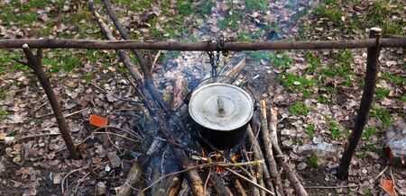 Cooking in old sooty cauldron on campfire at glade. Panoramic view. Stock fotó