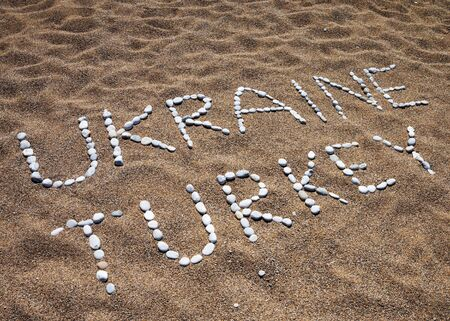 Words Ukraine, Turkey and smile composed of pebble stones on sand beach at summer Stock Photo