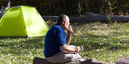 Man sitting on wooden log with mug of tea and cigarette. Hiker basks in sun, drinks tea and smokes cigarette. Sunlit light green camping tent and autumn forest at background. Panoramic view.
