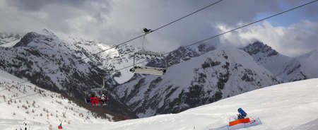 Chair-lift, snowy ski track prepared by snowcat, skiers on ski resort. High winter mountains and blue cloudy sky. Ski area Mottolino, Italian Alps. Livigno Lombardy, Italy Europe. Panoramic view.