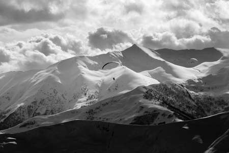 High snowy mountains and cloudy sky at winter evening. Silhouette of skydiver. Caucasus Mountains. Georgia, region Gudauri. Black and white toned image. High contrast.