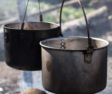Cooking in two sooty old cauldrons on campfire at sunny day. Close up view.