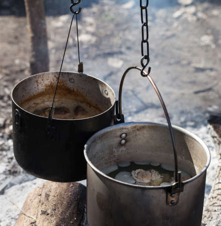 Cooking in two sooty old cauldrons on campfire at forest. Close-up view.