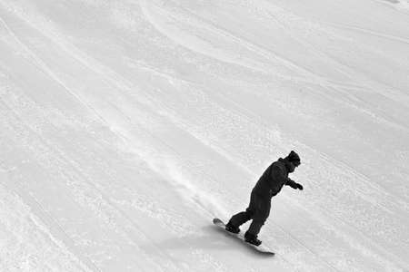 Snowboarder downhill on snow grooming ski slope at cold winter day. Black and white toned image.