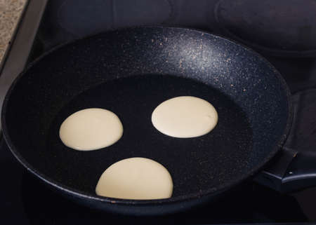 pancakes instruction step by step.step 2 put the dough in a pan. Pancakes are fried in a black frying pan, the mistress puts a dough with a spoon.