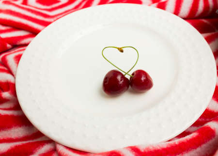 the concept of love - heart from berries of a sweet cherry.Isolated cherry. Heart shape from two cherries isolated white background.
