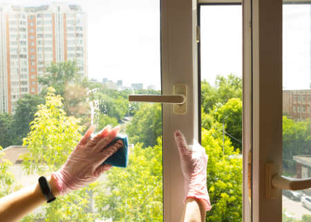 A woman polishing glass using a cleaning sponge and rubber gloves cleaning a window.the girl is cleaning the house