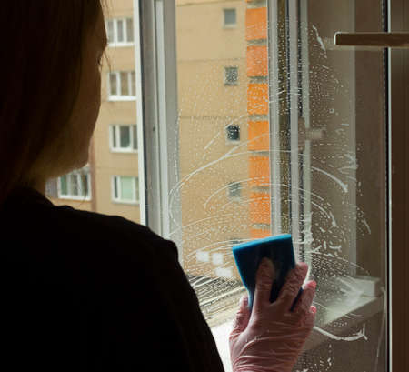 A woman polishing glass using a cleaning sponge and rubber gloves cleaning a window.the girl is cleaning the house.