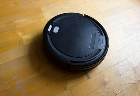 Robot vacuum cleaner on laminate wood floor, Smart robotic automate wireless cleaning technology machine in living room
