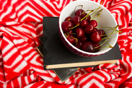The book and red ripe cherries. Two ripe cherries look out of the book. Cherries as an unusual bookmark for the book. Notebook for Recipes and Cherries.the concept of summer vacation and relax. 写真素材