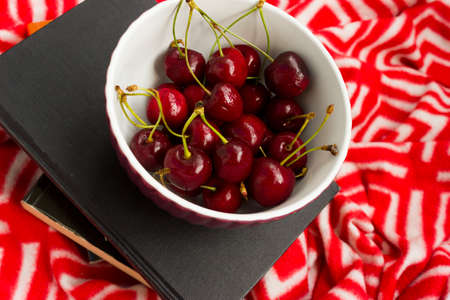 The book and red ripe cherries. Two ripe cherries look out of the book. Cherries as an unusual bookmark for the book. Notebook for Recipes and Cherries.the concept of summer vacation and relax. Foto de archivo