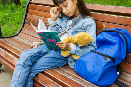 tired girl child schoolgirl sitting on a bench with a backpack and looking at a book. back to school