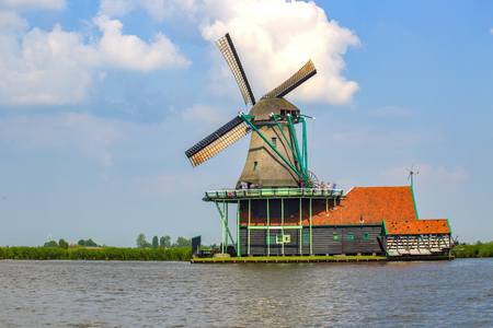 water mill: Beautiful Dutch sunny day with windmill at Kinderdijk and river side