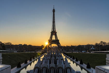 Early morning sunrise behind and in the middle of the Eiffel tower with the reflection on the fountain water of the Trocadero place in Paris