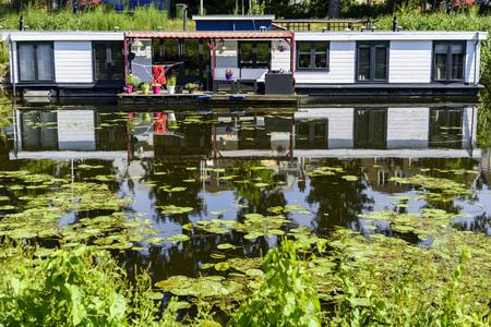 Weergave van drijvende huizen gebouwd op de lange van een kalm kanaal als gevolg van de opwarming van de aarde en de verhoging van het waterniveau rond de wereld wordt realiteit en concept Stockfoto