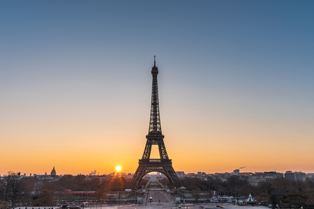 Landscape view of a warm sunrise over Paris and the Eiffel tower with a beautiful orange to blue gradient color