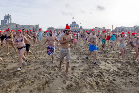 SCHEVENINGEN, 1 January 2018 - Ma messaging with his smartphone and running to his  first new year dip in the frozen North Sea water, The Netherlands