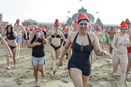 SCHEVENINGEN, 1 January 2018 - Dutch people following the strong tradition of the first new year dive runs toward the frozen North Sea water after the midday ring bells