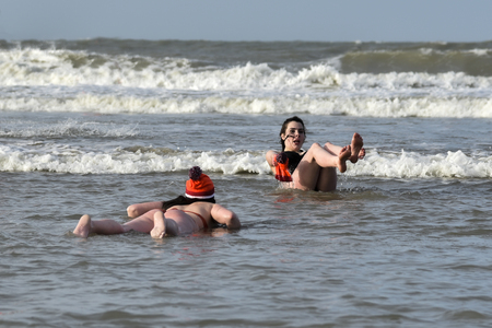 SCHEVENINGEN, 1 January 2018 - two girls laying and rolling on the beach for their first new year dip in the frozen North Sea water, The Netherlands