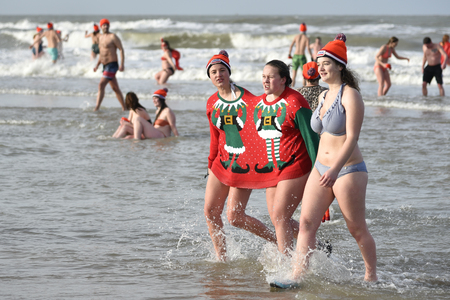 SCHEVENINGEN, 1 January 2018 - A group of Dutch girl wrapped in an single pull-over returning to the changing room after their first new year dip in the frozen North Sea water, The Netherlands
