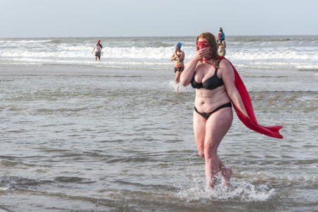 SCHEVENINGEN, 1 January 2018 - Strong girl disguised with a mask and cape getting to the beach after having accomplished the new year dive in a frozen North Sea water at Unox new year dive Editorial