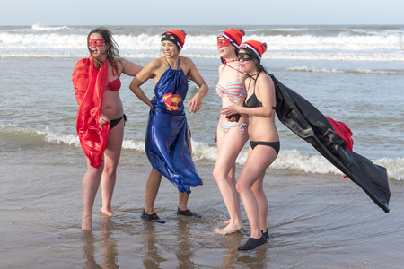 SCHEVENINGEN, 1 January 2018 - Group of friends posing for photographers in the water after having accomplished the new year dive in a frozen North Sea water