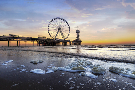 Landscape of a sunset at the beach and the pier of Scheveningen with nobody, no tourists, The Hague, Netherlands Stock Photo