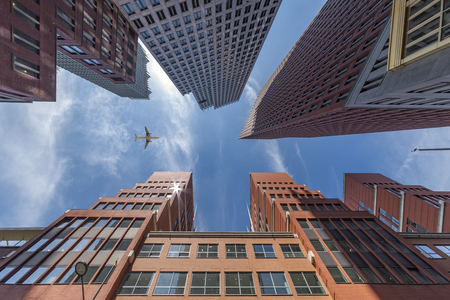 A plane flying over the modern blue cubic buildings located at The Hague city, Netherlands