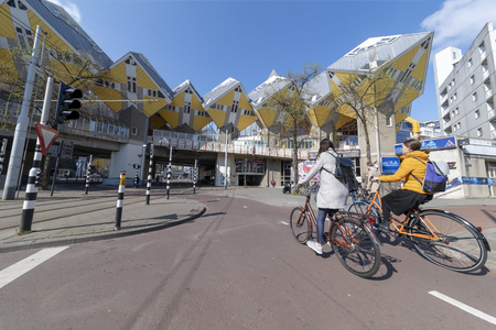 ROTTERDAM, 13 April 2019 - Cyclists riding rapidly on the cyclist path though the Cubic houses under a sunny blue sky