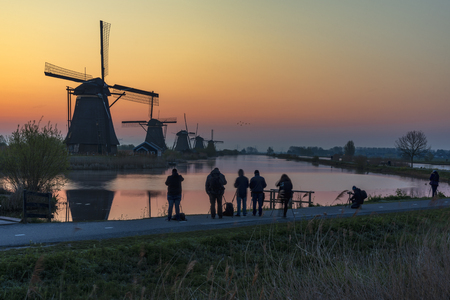 Silhouette of photographers standing and capturing pictures in front the Kinderdijk windmill sunrise during the golden hour, Alblaserdam, Netherlands