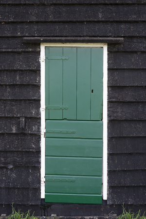 Front door of small rural cottage house with wooden wall and green door