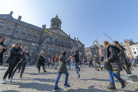 AMSTERDAM, 14 April 2019 - Water balloon blower playing with kids and children on the Dam Square of Amsterdam under a sunny bright sky