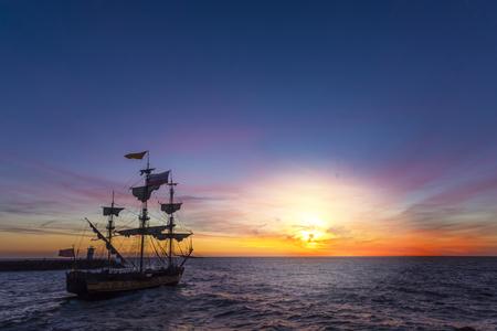 Silhouette eines Piratenschiffs, das den Hafen für eine lange Kampagne auf dem Ozean verlässt, um andere Marschschiffe mit Kopienraum zu pirschen Standard-Bild