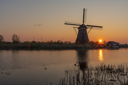 Sunrise on the alignment of windmills reflected on the calm water in the long canal Banque d'images