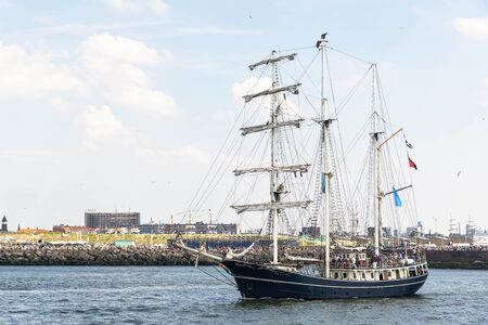 Antique tall ship, vessel leaving the harbor of The Hague, Scheveningen under a sunny and blue sky Archivio Fotografico