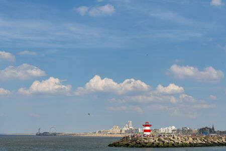 Panoramic view of the Scheveningen lighthouse, the entrance of the dock or the harbor against the pier under a sunny blue sky weather