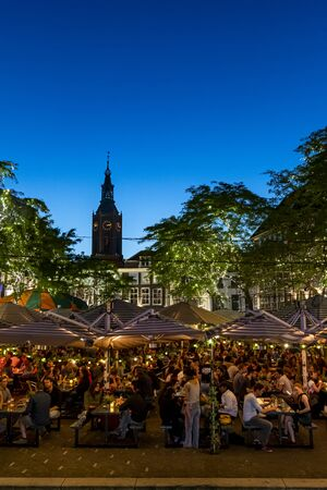 THE HAGUE, 28 June 2019 - City center restaurant bar crowded of people drinking and dining at the blue hour moment Stock Photo
